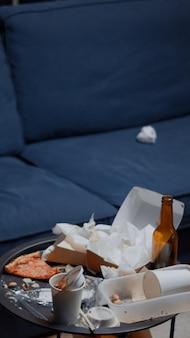 Chaos im leeren wohnzimmer mit essensmüll, flasche bier und servietten auf blauem sofa