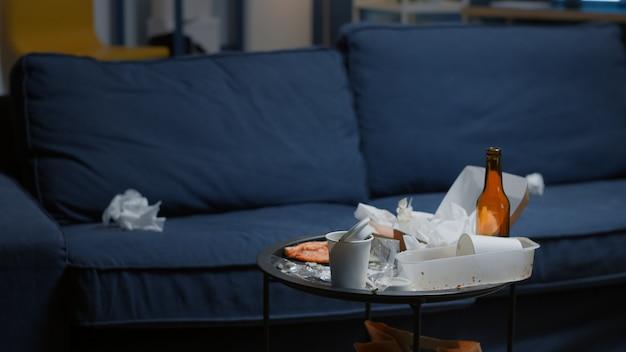 Chaos im leeren wohnzimmer mit essensmüllflasche bier und servietten auf blauem sofa unorganisiertes haus...