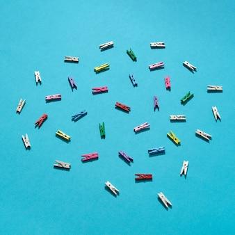 Chaotisch angeordnetes buntes wäscheklammernmuster auf einem blau mit harten schatten, kopienraum. flach liegen.