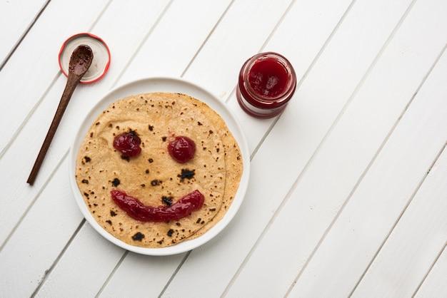 Chapati roll mit tomatenketchup oder fruit jam jelly mit smiley-gesicht, indisches kinder-lieblingsmenü für schultiffin-box, selektiver fokus