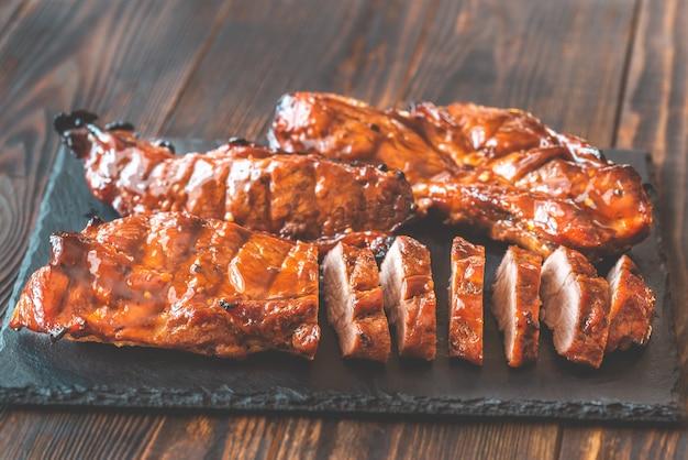 Char siu schweinefleisch - chinesisches grillschweinefleisch auf dem schwarzen steinbrett