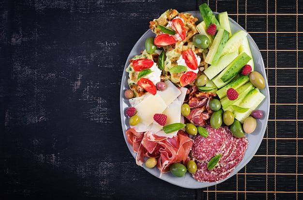 Charcuterie-brett. platte: parmesan mit prosciutto, salami, gurken und oliven. auswahl an leckeren vorspeisen oder antipasti. ansicht von oben, kopienraum, flache lage