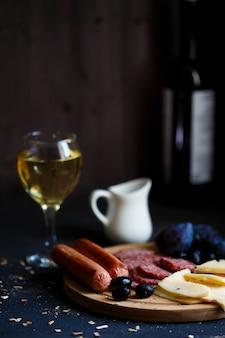 Charcuterie, gegrillte würstchen, käse, salami, pflaumenoliven und ein glas wein auf einem dunklen tisch