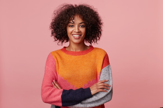 Charismatisch attraktives afroamerikanisches mädchen mit afro-frisur sieht mit vergnügen, mit angenehmem lächeln aus, steht mit verschränkten armen, trägt buntes langarm, isoliert auf rosa wand