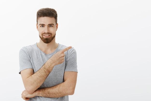 Charismatisch entzückter und selbstbewusster geschäftsmann, der geschäftsplan mit partner bespricht, der auf die obere rechte ecke zeigt lächelnd erfreut zeigt guten platz für kopierraum gegen weiße wand