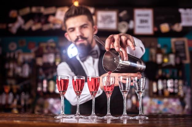 Charismatische barkeeperin mischt einen cocktail, während sie in der kneipe in der nähe der theke steht