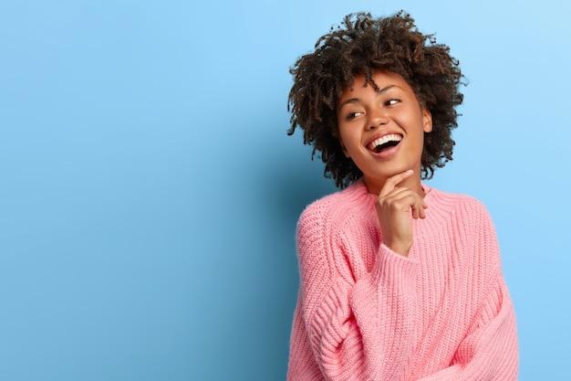 Charismatische frau mit einem afro, der in einem rosa pullover aufwirft