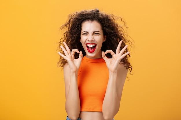 Charismatische, glückliche und fröhliche, attraktive junge frau mit lockiger frisur, die mit beiden händen zustimmende oder bestätigende gesten zeigt und glücklich über orangefarbene wand lächelt und lacht.