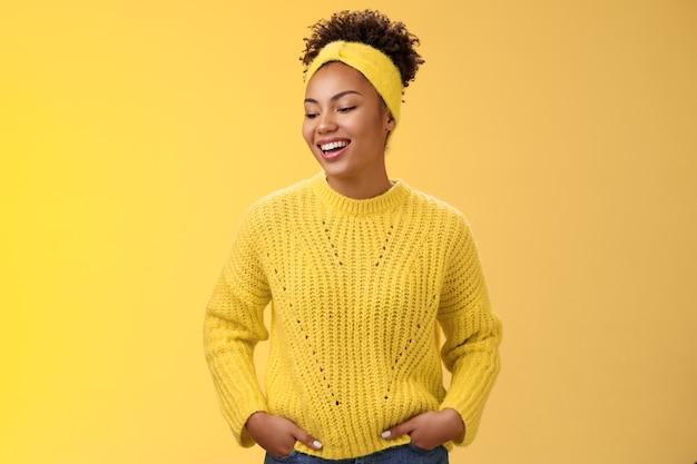 Charismatische, sorglose lifestyle-studioaufnahme afroamerikanische frau, die freundlich lacht, die nach links unten hält, die hände hält, die taschen selbstbewusst ungestörte entspannte pose, die auf gelbem hintergrund plaudert.