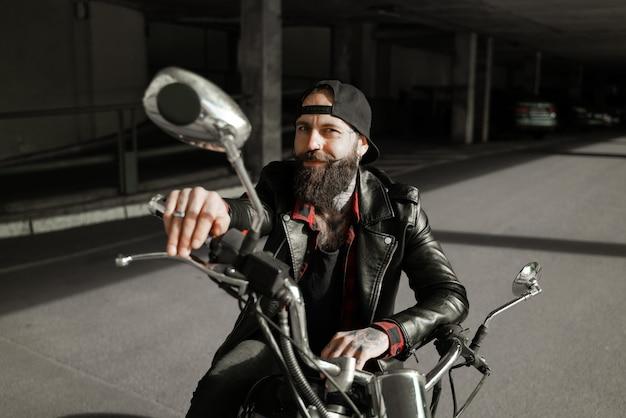 Charismatischer biker auf einem lächelnden motorrad