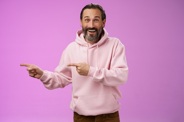 Charismatischer glücklicher gutaussehender reifer mann der 50er jahre, der stilvollen hipster-kapuzenpulli trägt, der aufgeregt zeigt, der linke zeigefinger zeigt beeindruckend beeindruckender interessanter vorschlag, der erfreut lila hintergrund steht.