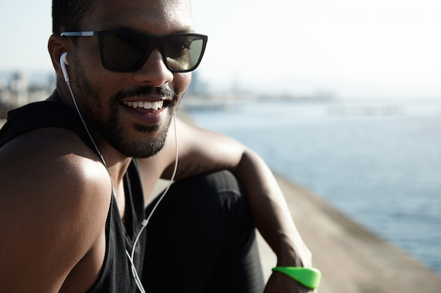 Charismatischer junger afrikanischer athlet, der trendige sonnenbrillen und schwarzes outfit trägt und glücklich und fröhlich am meer gegen blauen himmel und meer sitzt