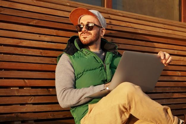 Charismatischer junger glücklicher männlicher freiberufler mit stoppeln, die auf holzbank mit tragbarem computer sitzen