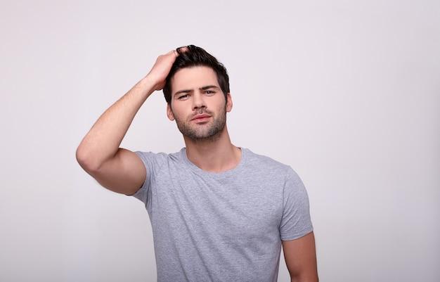 Charismatischer junger mann, der kamera betrachtet, während er gegen grau steht.