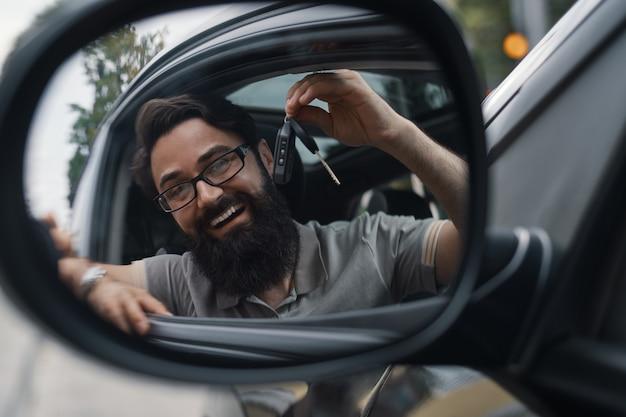 Charismatischer mann, der autoschlüssel hält