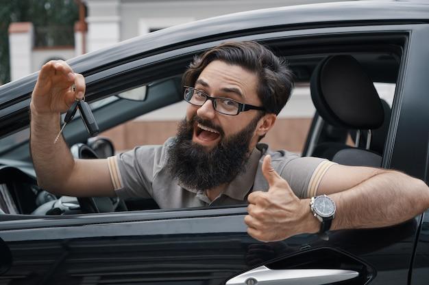 Charismatischer mann, der autoschlüssel mit daumen hoch hält