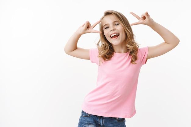 Charismatisches, fröhliches, lebhaftes, blondes, energisches kind, fröhliches mädchen, das frieden und sieg zeigt, fröhlich lächelt und sorglos mit den eltern spielt, ins ausland reisen kinderlager, spaß an der weißen wand haben