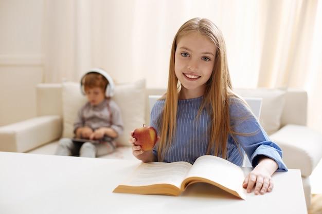 Charismatisches kluges entzückendes kind, das am tisch sitzt und etwas liest, während ein apfel für einen snack hat