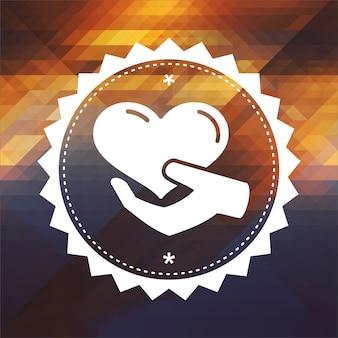 Charity concept - ikone des herzens in der hand. retro-etikettendesign. hipster hintergrund aus dreiecken, farbfluss-effekt.