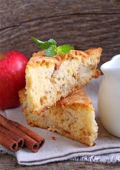 Charlotte mit äpfeln in der weißen platte auf einem hölzernen hintergrund