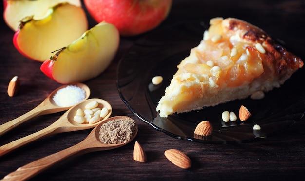 Charlotte mit äpfeln und nüssen. vorbereitung des apfelbackens mit nüssen und honig. dessert-backwaren aus äpfeln und nüssen mit honig auf einem holztisch.