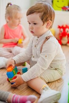 Charmanischer junge im kindergarten mit anderen kindern