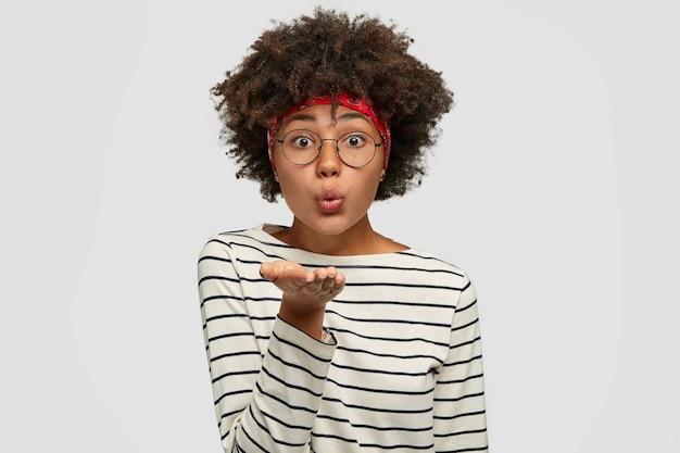 Charmante afroamerikanische frau sendet luftkuss, hält handfläche zum mund