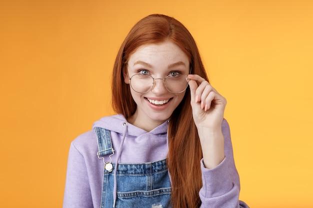 Charmante alberne, bescheidene junge rothaarige weibliche geek-spieleliebhaberin diskus letzte gaming-trends, die glücklich lächeln, amüsiert touch-brille, die neugierig grinst, erhalten süßes geschenk überrascht, orangefarbener hintergrund