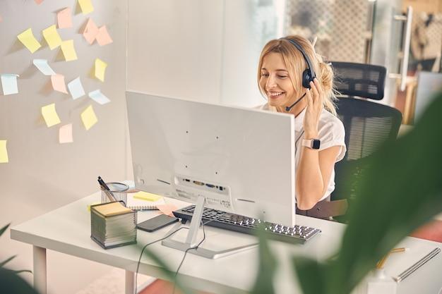Charmante arbeiterin, die einen modernen computer verwendet und lächelt, während sie bei der arbeit am tisch sitzt