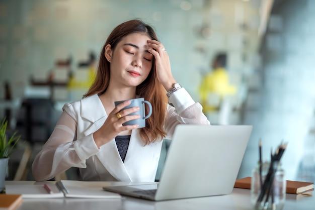 Charmante asiatische büroangestellte, die an einem laptop arbeitet und kaffee in einem modernen büro trinkt