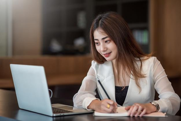 Charmante asiatische geschäftsfrau, die am laptop arbeitet und zur kenntnis nimmt, während sie am tisch im büro sitzt