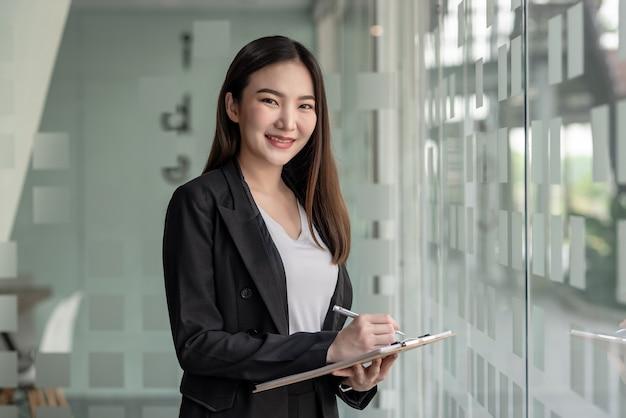 Charmante asiatische geschäftsfrau, die ein dokument in der nähe eines spiegels in einem büro hält.