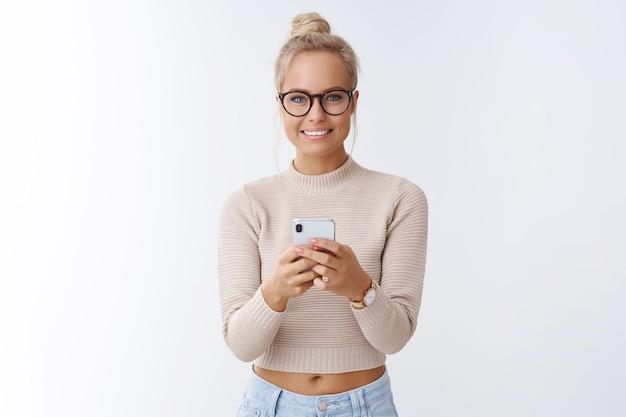 Charmante attraktive europäische frau mit brötchenfrisur in brille mit smartphone, die optimistisch lächelt und optimistisch ein foto auf dem handy zeigen möchte, das amüsiert vor weißem hintergrund posiert