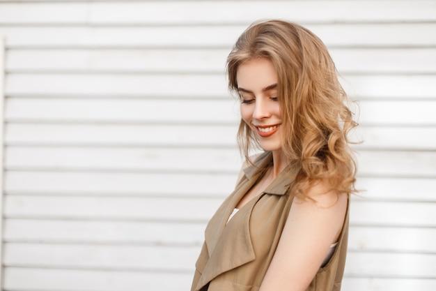 Charmante attraktive junge frau mit einem schönen lächeln in stilvollen sommerkleidern steht in der nähe einer weißen holzweinwand im freien. nettes glückliches positives modisches mädchen.