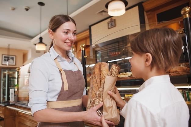 Charmante bäckerin, die ihren jungen kunden anlächelt und ihm frisches brot gibt
