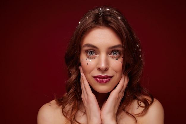 Charmante blauäugige junge braunhaarige dame mit gewellter frisur, die ihr gesicht mit erhobenen händen hält und mit gefalteten lippen schaut, mit festlichem make-up stehend