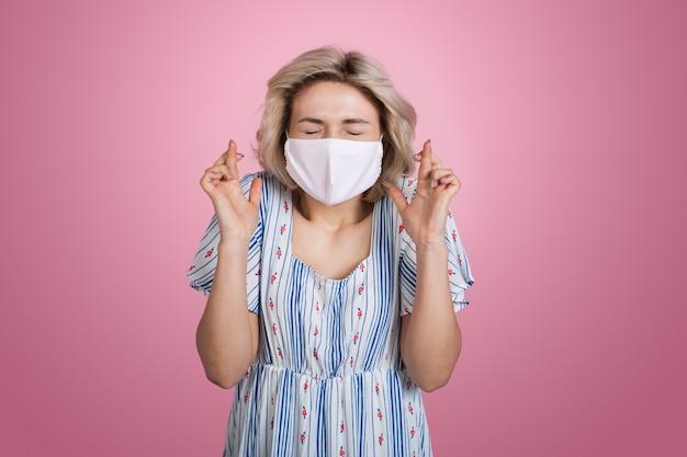 Charmante blonde dame im sommerkleid mit medizinischer maske auf gesicht gestikuliert einen traum auf einer rosa wand