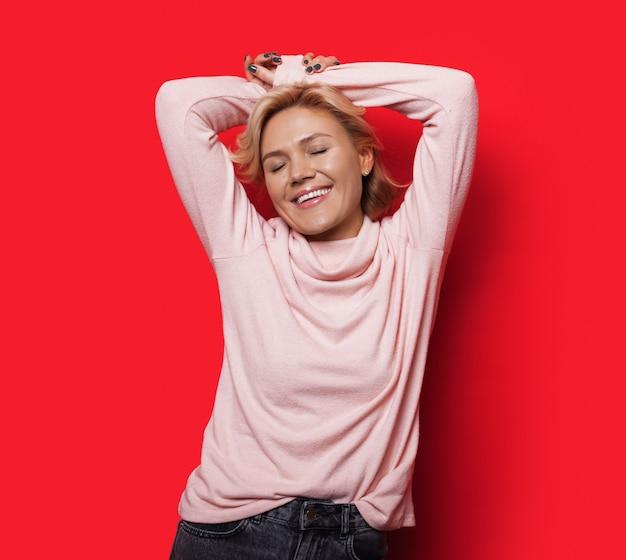 Charmante blonde dame posiert mit den händen über dem kopf