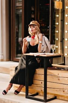 Charmante blonde frau, die auf holzbank neben restaurant sitzt und lieblingsgetränk genießt. außenporträt des prächtigen mädchens im mantel und in der kappe, die kaffee trinken und jemanden warten.