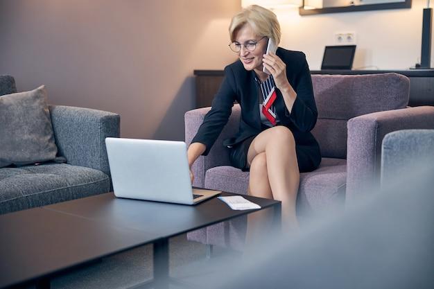 Charmante blonde frau, die telefongespräche führt und lächelt, während sie im sessel sitzt und im hotelzimmer am notebook arbeitet?