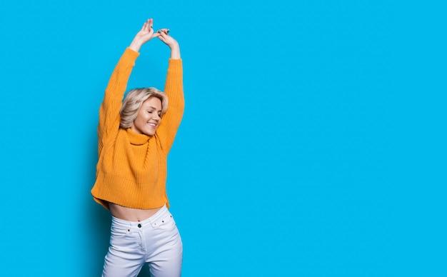 Charmante blonde frau im gelben strickpullover, der auf einer blauen studiowand mit freiem raum lächelt