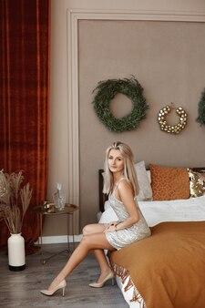 Charmante blonde frau in einem kurzen kleid sitzt in der nähe des weihnachtsbaumes