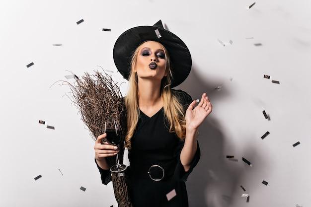 Charmante blonde hexe, die wein genießt. fröhliche blondhaarige dame im maskeradenkostüm, das auf halloween-partei aufwirft.