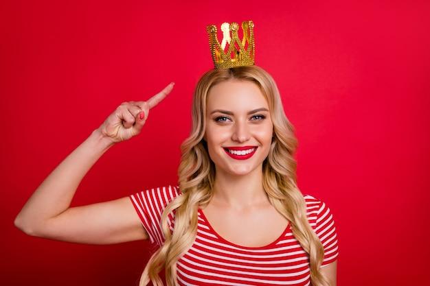 Charmante blonde junge mädchen abschlussballkönigin tragen goldenen diadem direkten fingerkopf