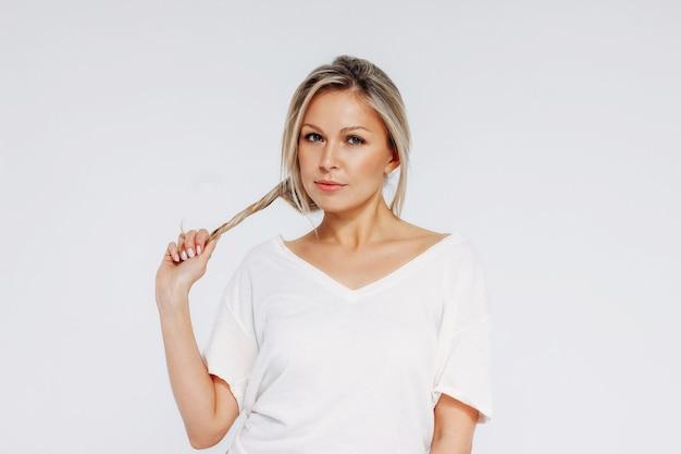 Charmante blonde lächelnde frau 35 jahre plus sauberes frisches hautgesicht mit haltendem haar und blick auf kamera lokalisiert auf weißem hintergrund