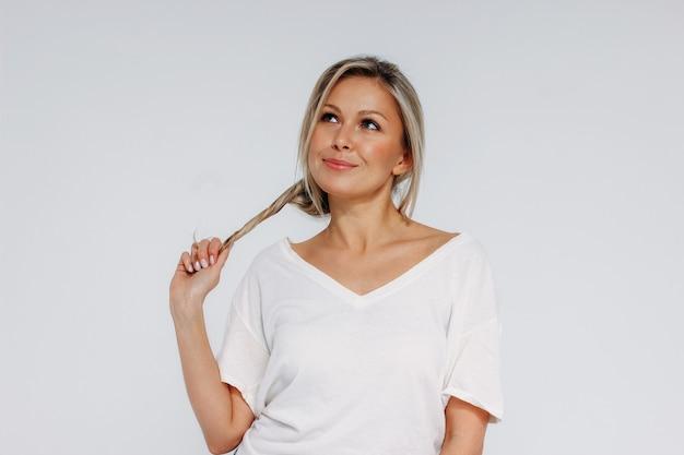 Charmante blonde lächelnde frau 35 jahre plus sauberes frisches hautgesicht mit haltendem haar und nach oben lokalisiert auf weißem hintergrund