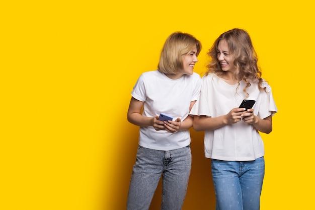Charmante blonde schwestern lächeln sich gegenseitig an, posieren auf einer gelben wand und chatten auf handys