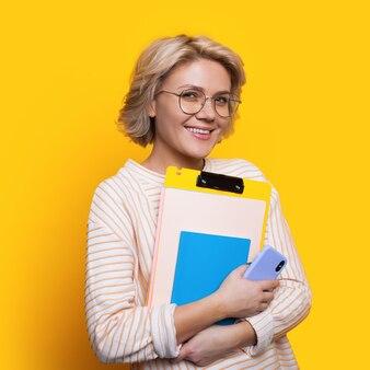 Charmante blonde studentin mit brille, die einige ordner hält, die an der kamera auf einer gelben wand lächeln