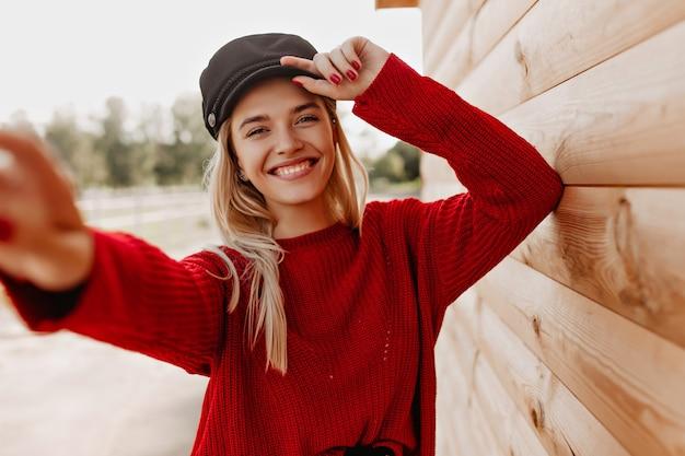 Charmante blondine in rotem pullover und dunklem hut, der glücklich an ihrem telefon lächelt. hübsches mädchen, das selfie nahe holzhaus im freien macht.