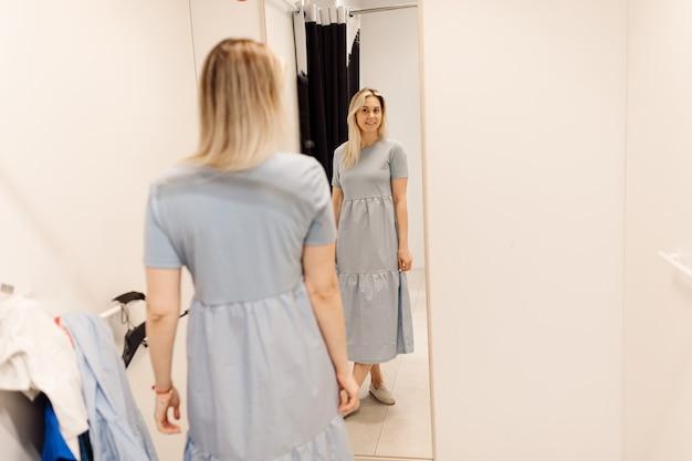 Charmante blondine mag sich wirklich im spiegel der umkleidekabine im supermarkt